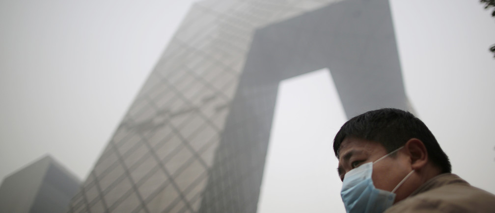 A man wearing a mask walks on a street on a hazy day in Beijing October 24, 2014. REUTERS/Kim Kyung-Hoon (CHINA - Tags: ENVIRONMENT SOCIETY) - GM1EAAO1ENZ01
