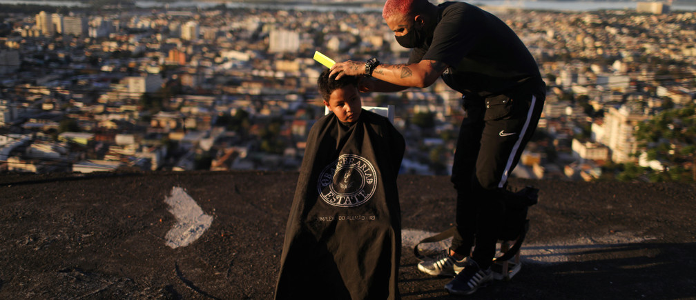 """Barber Renan Estate gives a haircut to a child at home as part of his """"Delivery Barber"""" service, as his shop is closed due to the coronavirus disease (COVID-19) outbreak, in the Complexo do Alemao slum in Rio de Janeiro, Brazil June 22, 2020. REUTERS/Pilar Olivares - RC2NEH9EJ26N"""