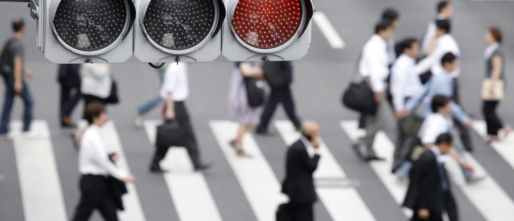 A traffic light is seen while pedestrians cross a street in Tokyo August 3, 2009.   REUTERS/Stringer (JAPAN BUSINESS EMPLOYMENT) - GM1E58J0UGT01