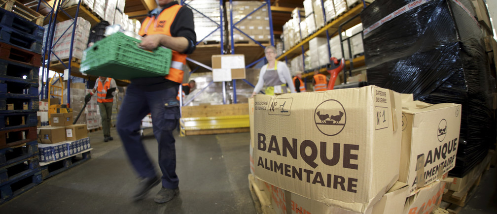 """Volunteers at the """"Banques Alimentaires"""" (Food Bank) move palettes in their warehouse in Arcueil, France, May 26, 2015. France is cracking down on food waste with legislation banning supermarkets from destroying unsold but edible food on pain of fines and even jail sentences. The new bill is to be voted on by France's lower house of parliament on May 26 and then sent to the Senate.   REUTERS/Philippe Wojazer - RTX1EKSV"""