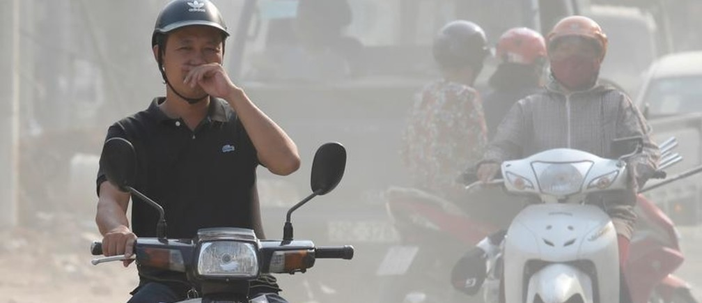 A man covers his nose as he drives through an air polluted street in Hanoi, Vietnam October 1, 2019. REUTERS/Kham - RC1CC4679CB0