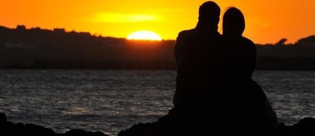 A couple watch the sun setting on a beach near Holyhead in Anglesey, north Wales May 1, 2011. Britain's Prince William, the Duke of Cambridge, is stationed as a helicopter pilot on Anglesey and will return to work this week following his marriage to Kate Middleton, the Duchess of Cambridge, on April 29. REUTERS/Toby Melville (BRITAIN - Tags: ENVIRONMENT SOCIETY ROYALS)