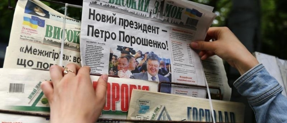 "People pick up copies of newspapers a day after Ukrainian presidential election at a newsstand in the western Ukrainian city of Lviv May 26, 2014. Ukraine's next president, Poroshenko, said on Monday he would not negotiate with armed separatists in the Russian-speaking east of his country but was open to dialog with people there with grievances, provided they rejected violence. The newspaper (C) headline reads, ""New President - Petro Poroshenko."" REUTERS/Kacper Pempel (UKRAINE  - Tags: POLITICS ELECTIONS) - GM1EA5Q1FOC01"