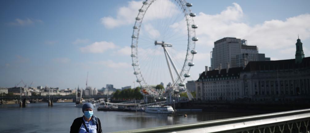 Una mujer con una máscara protectora en el puente de Westminster en Londres tras el brote de la enfermedad coronavirus (COVID-19), Londres, Gran Bretaña, 6 de mayo de 2020