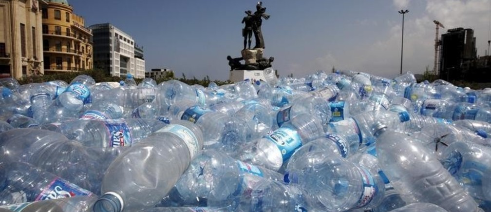 Water bottles are gathered to be recycled near a statue in Martyrs' Square in Beirut, Lebanon August 25, 2015.  Lebanon's cabinet held an emergency meeting on Tuesday in its newly fortified headquarters after protests over trash collection spilled over into street violence and calls for the feuding government to resign. REUTERS/Jamal Saidi      TPX IMAGES OF THE DAY      - GF10000182062