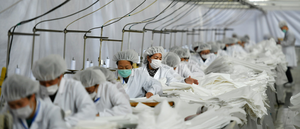 Employees work on a production line manufacturing protective suits at a clothing factory, as the country is hit by an outbreak of the novel coronavirus, in Shijiazhuang, Hebei province, China February 17, 2020. Picture taken February 17, 2020. cnsphoto via REUTERS   ATTENTION EDITORS - THIS IMAGE WAS PROVIDED BY A THIRD PARTY. CHINA OUT. - RC2V2F9YQ0Y0