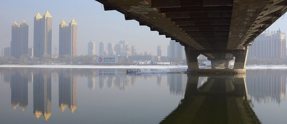 Newly-built residential buildings are seen next to the partially-frozen Songhua River and a bridge in Jilin, Jilin province February 3, 2015. Fourteen Chinese provinces plan to invest a combined 15 trillion yuan ($2.4 trillion) in infrastructure and other projects starting this year as part of their effort to help set a bottom on a slowdown in the economy, an official newspaper said on Wednesday. Picture taken February 3, 2015. REUTERS/Stringer (CHINA - Tags: BUSINESS CONSTRUCTION ENVIRONMENT REAL ESTATE) CHINA OUT. NO COMMERCIAL OR EDITORIAL SALES IN CHINA - RTR4O590