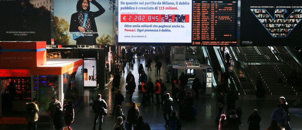 """People walk past a """"debt clock"""" screen, installed by Bruno Leoni Institute's analysts, displaying Italy's public debt at the Termini central station in Rome, Italy February 15, 2018. REUTERS/Alessandro Bianchi - RC1AFF944460"""