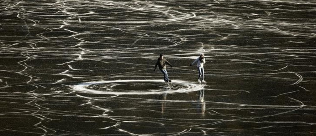 A couple skates on the frozen waters of Lake St. Moritz during a sunny winter day in the Swiss mountain resort of St. Moritz December 14, 2013.  REUTERS/Arnd Wiegmann  (SWITZERLAND - Tags: SOCIETY ENVIRONMENT TPX IMAGES OF THE DAY)