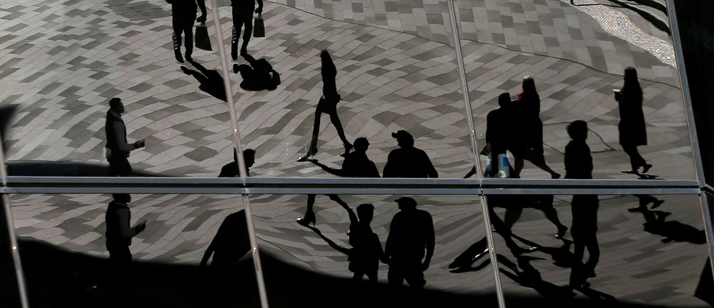 Workers are reflected in an office building's windows in Sydney's Barangaroo business district