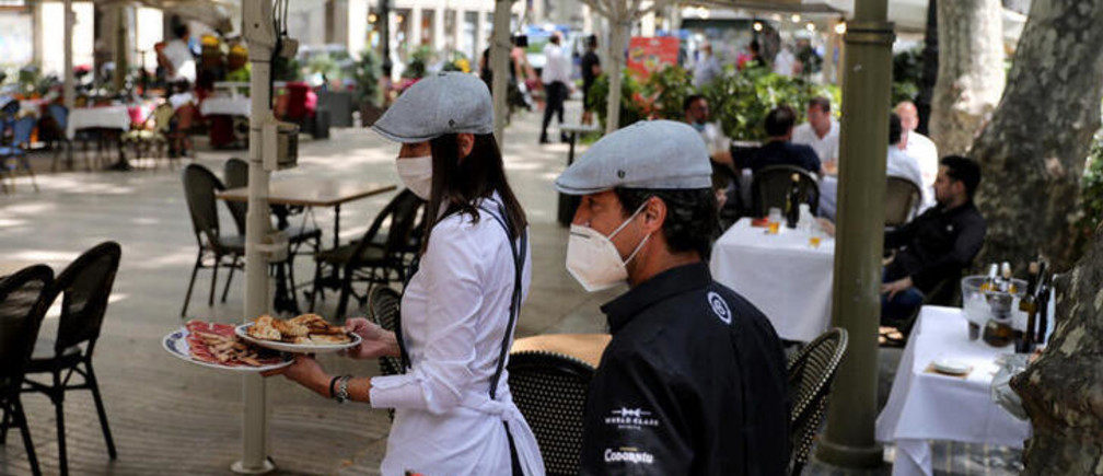 Waiters wearing protective face masks carry food for clients at an outdoor seating section of a restaurant at Ramblas, as some Spanish provinces are allowed to ease lockdown restrictions during phase one, amid the coronavirus disease (COVID-19) outbreak, in Barcelona, Spain, May 25, 2020.