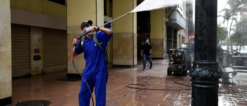 A municipal worker cleans with a power washer after Ecuador's government restricted travel within the country and declared a nighttime curfew as a response to curb the spread of the coronavirus disease (COVID-19), in Guayaquil, Ecuador March 17, 2020.