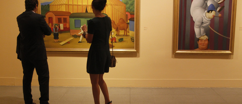 """People look at a painting by Colombian painter and sculptor Fernando Botero during the opening of his exhibition """"The Circus"""" at the Museum of Antioquia"""