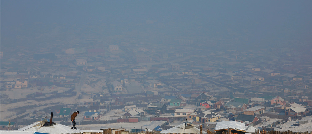 """A man walks on the roof of a traditional ger home while fixing the chimney of a coal burning stove on a cold hazy day on the outskirts of Ulaanbaatar, Mongolia January 19, 2017. REUTERS/B. Rentsendorj  SEARCH """"RENTSENDORJ POLLUTION"""" FOR THIS STORY. SEARCH """"WIDER IMAGE"""" FOR ALL STORIES.   TPX IMAGES OF THE DAY - RC173A927F20"""