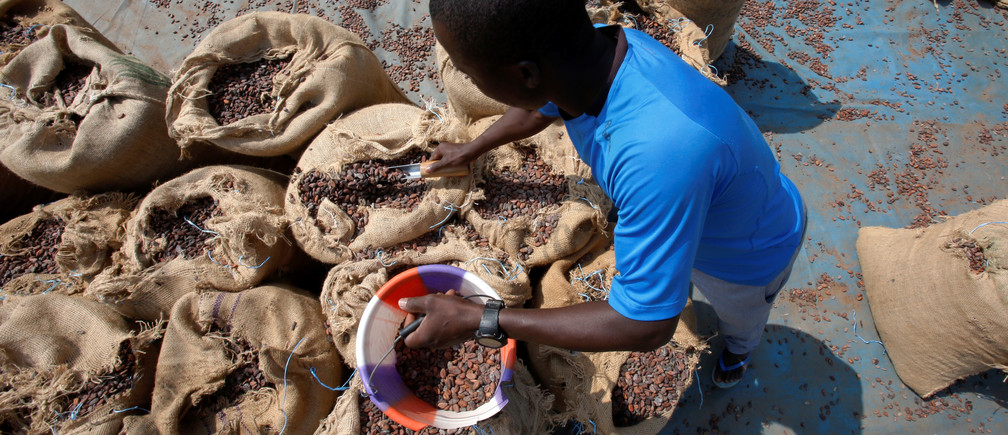 A man prepares sacks of cocoa beans to be sealed in Soubre, Ivory Coast July 19, 2018. Picture taken July 19, 2018. REUTERS/Thierry Gouegnon - RC187285D100