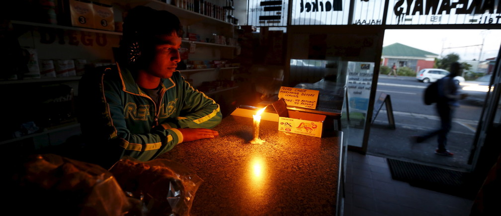 A shopkeeper waits for customers in his candlelit fast food store during a load shedding electricity blackout in Cape Town April 15, 2015.