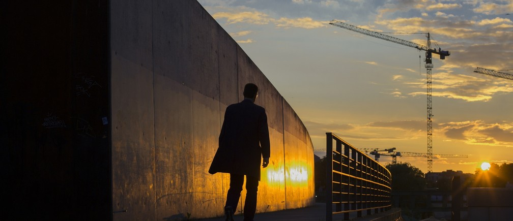 A man walks along the embankment of the river Spree during sunset in Berlin, September 13, 2013.