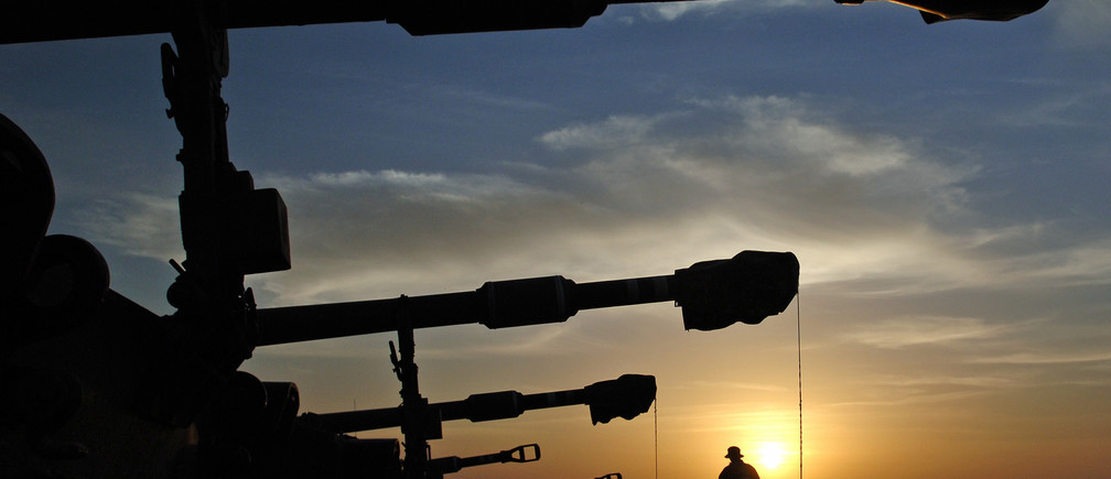 An Israeli soldier walks in front of mobile artillery units on the field near the kibbutz of Nahal Oz, outside the northern Gaza Strip, January 3, 2006. REUTERS/Amir Cohen - RP3DSFEAJHAB