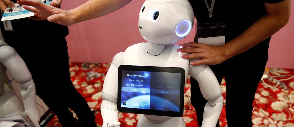 A man touches SoftBank humanoid robot known as Pepper as he demonstrates its translation function at Pepper World 2016 Summer during SoftBank World 2016 conference in Tokyo, Japan, July 21, 2016.