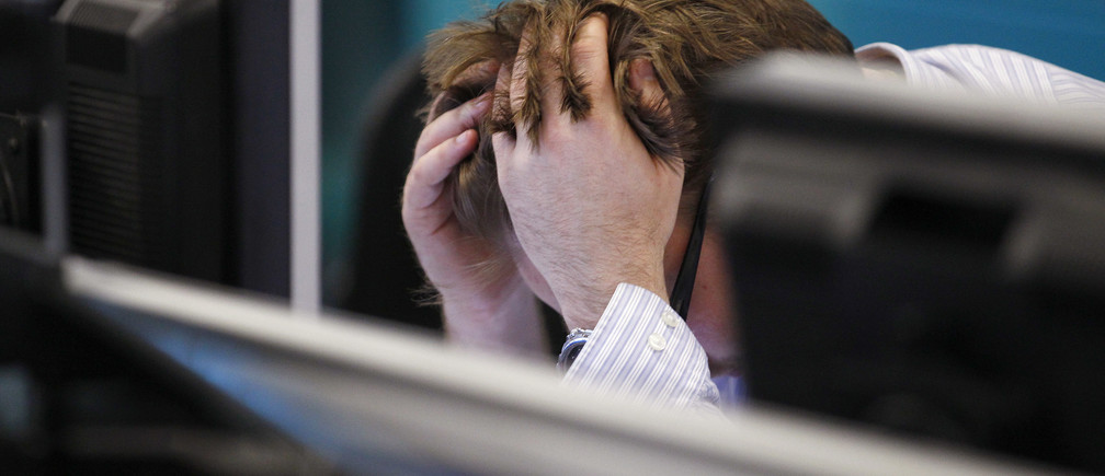 A worker on IG Index's trading floor holds his head in his hands as markets tumble globally, in London September 22, 2011. World stocks and commodities tumbled on Thursday as weak data from China crystallized investor fears about a global recession one day after a grim economic outlook from the U.S. Federal Reserve. Stocks tumbled more than 4 percent and commodities took a beating. Weak data from Germany and China helped push investors to safe U.S. government bonds, where benchmark yields again touched lows not seen in 60 years. REUTERS/Andrew Winning (BRITAIN - Tags: BUSINESS)