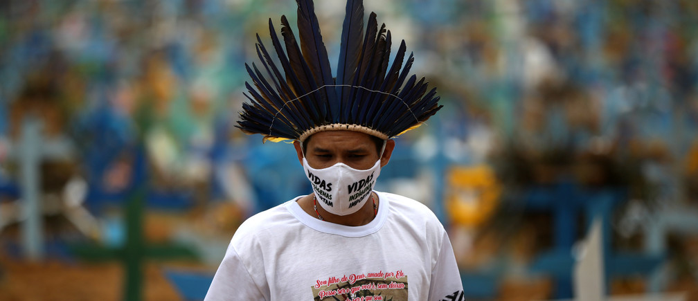 "Indigenous person Miqueias Moreira Kokama, wears a protective face mask with words that read:""Indigenous lives matter"", during a visit to his father's grave, indigenous Chief Messias Kokama, who passed away due to the coronavirus disease (COVID-19), at the Parque Taruma cemetery in Manaus, Brazil, May 26, 2020. REUTERS/Bruno Kelly - RC2IWG9QOGAR"