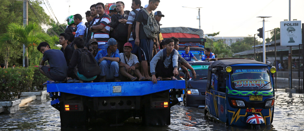 Workers being transported at the back of a truck on a flooded street after high tide hit Muara Baru area in Jakarta, Indonesia, December 6, 2017.  REUTERS/Beawiharta - RC1E55986540