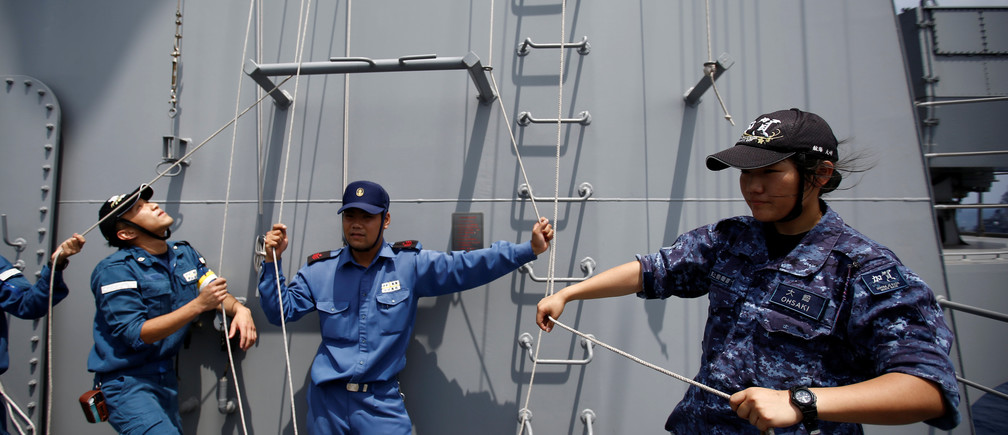 A female navigator on board a Japanese helicopter carrier practices raising signal flags.