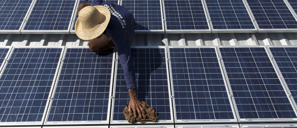 Francisco da Silva Vale, 61, cleans solar panels at an ice production facility in Amazonas state, Brazil.