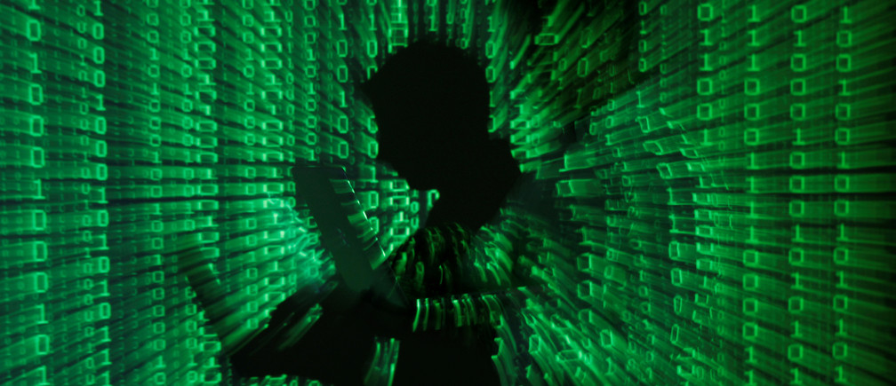 An illustration picture shows a projection of binary code on a man holding a laptop computer, in an office in Warsaw June 24, 2013. REUTERS/Kacper Pempel/Illustration/File Photo - S1AETKWRHTAA