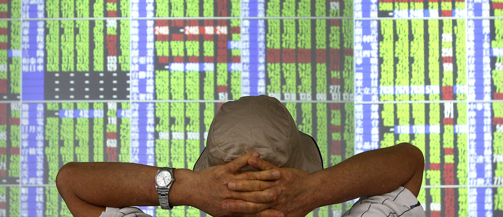 A man monitors stock prices inside a brokerage in Taipei September 6, 2011.