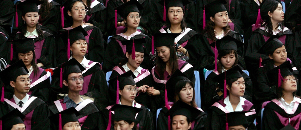 Two graduates play during a graduation ceremony at Tsinghua University in Beijing, July 11, 2006.  About 4.1 million are expected to graduate this year, an increase of 22 percent over 2005, the official Xinhua news agency reported.  REUTERS/Jason Lee (CHINA) - RTR1FDWL