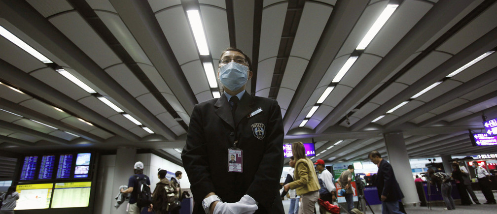 A health worker stands by ready to ask incoming passengers to remove any head gears before temperature screenings at the International Airport in Hong Kong April 27, 2009. Asia, a continent that has battled deadly viruses such as the H5N1 bird flu and SARS in recent years, began taking steps over the weekend to ward off a new flu virus.   REUTERS/Vincent Yu/Pool   (CHINA POLITICS HEALTH IMAGES OF THE DAY) - GM1E54R15DW01