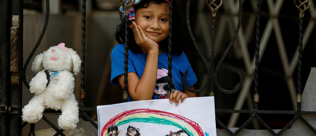 "Jemima Christa-Faelist Tanamal, 6, poses for a photograph while holding a picture that she drew during the coronavirus disease (COVID-19) outbreak, while standing by her grandparents house in Bekasi, Indonesia, April 21, 2020. Jemima drew herself and her little brother going for a picnic with their grandparents. ""I don't like to stay at home, boring,"" said Jemima. ""Once I can go outside, I will go to the mini-market for bubble gum first. I like to go to school, because I can play together with my friends. I will hug my friends and teachers when I go back to school later and say 'I miss you teacher, I miss you friend' to them."" REUTERS/Willy Kurniawan      SEARCH ""CORONAVIRUS DRAWING"" FOR THIS STORY. SEARCH ""WIDER IMAGE"" FOR ALL STORIES.   REFILE - CLARIFYING INFORMATION - RC2BAG9LYF2Z"