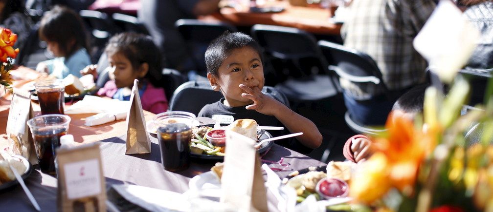 A boy eats an early Thanksgiving meal served to the homeless at the Los Angeles Mission in Los Angeles, California, November 25, 2015.