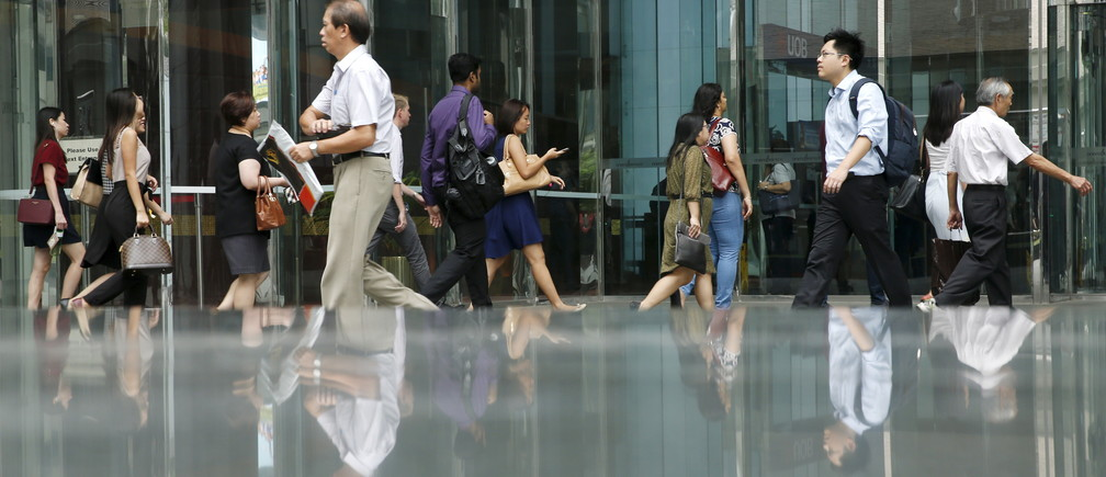 Office workers walk to work during morning peak hour commute in the central business district in Singapore March 24, 2016
