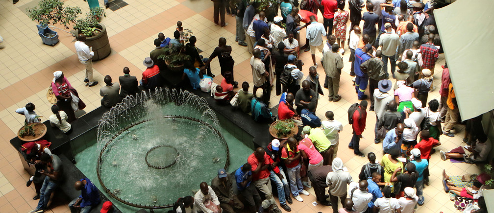 People queue to withdraw money from a bank in Harare, Zimbabwe's capital, March 8, 2017. REUTERS/Philimon Bulawayo - RC1F6315AB10