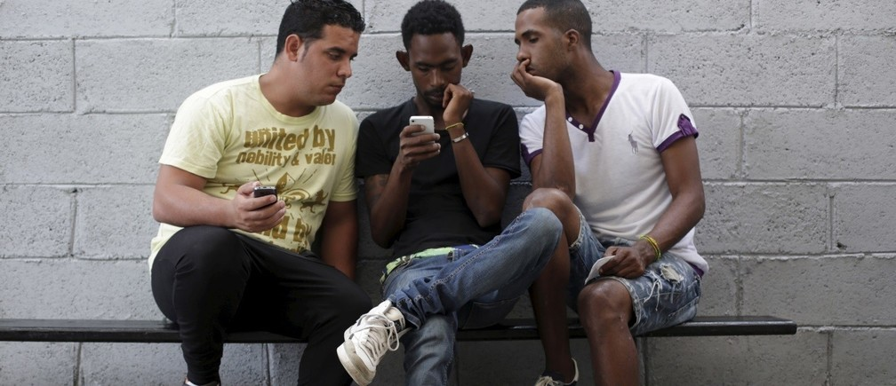 "Young people use the internet via the free wifi at the studio of Cuban artist Alexis Leyva ""Kcho"" in Havana"