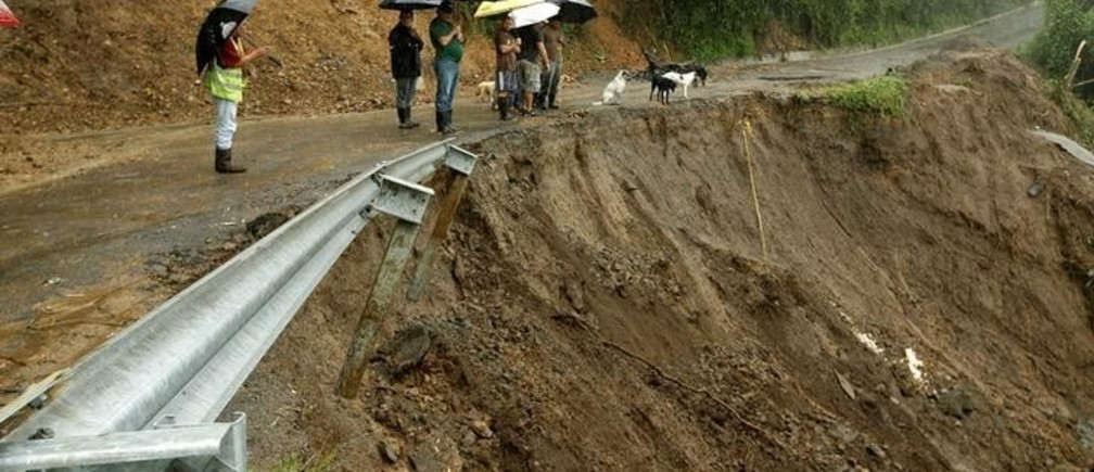 Residents look ta road partially collapsed by heavy rains of Tropical Storm Nate that affects the country in El Llano de Alajuelita, Costa Rica October 5, 2017. REUTERS/Juan Carlos Ulate