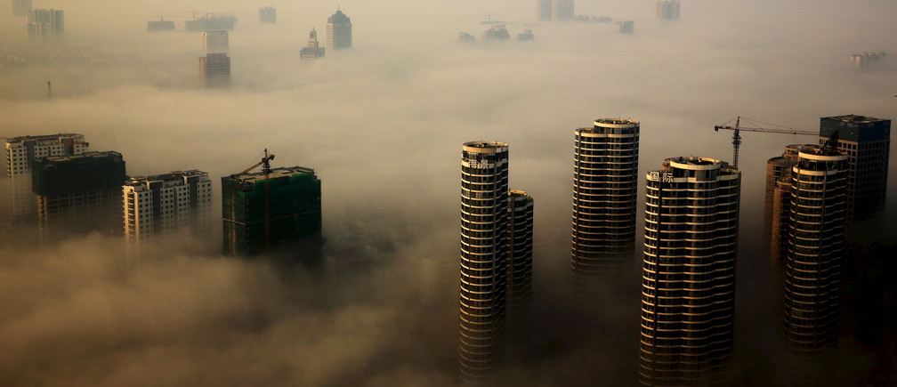 Buildings in construction are seen among mist during a hazy day in Rizhao, Shandong province, China, October 18, 2015. REUTERS/Stringer CHINA OUT. NO COMMERCIAL OR EDITORIAL SALES IN CHINA      TPX IMAGES OF THE DAY      - GF10000249104