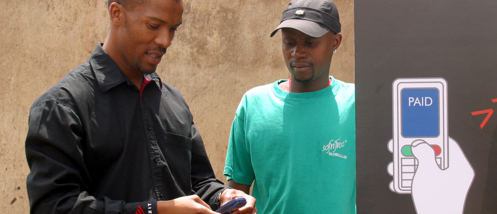 Dumisani Mntambo (L), sales and marketing personnel for Wizzit cell phone banking, consults with client Mphikeleli Ngwenya, a hair salon owner in Johannesburg's Soweto township October 19, 2005. Mobile technology has already revolutionised communications in the world's poorest continent, bringing phones to millions of poor and isolated people who had never before made a call. Now cell phones are serving as a bank in your pocket, providing virtual accounts for South Africans excluded from the financial mainstream by exorbitant charges and branch networks clustered in wealthy white suburbs. Picture taken October 19, 2005.