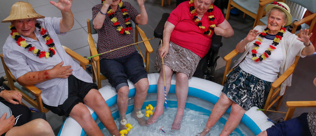 Residents at the Ter Biest house for elderly persons refresh their feet in a pool on a hot summer day, in Grimbergen, Belgium, August 3, 2018. REUTERS/Yves Herman - RC123F5D8240