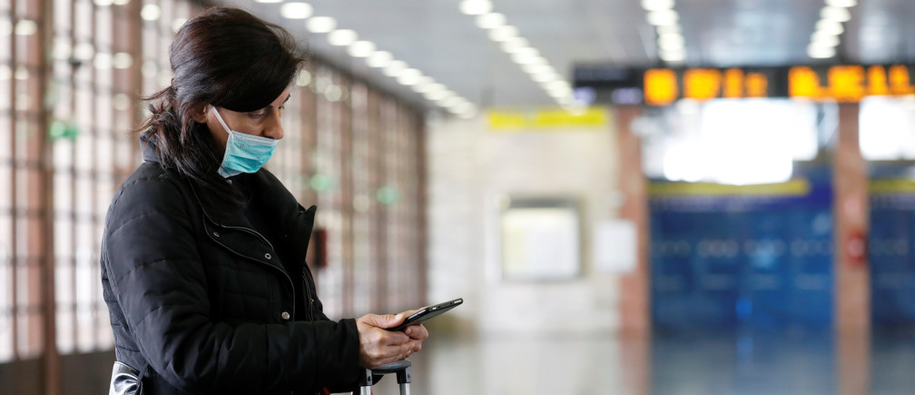 A woman in a protective mask checks her phone at the Messina Station in the Sicilian city of Messina after Sicily requested that transport to the island would be blocked from mainland Italy as part of measures to contain coronavirus contagion on the island, in Messina, Italy March 16, 2020. REUTERS/Antonio Parrinello - RC2ZKF9GSWSH