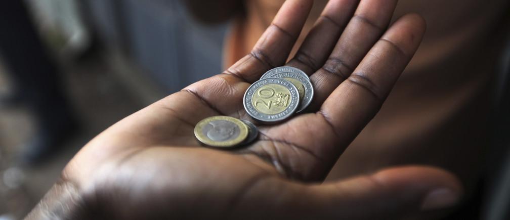A customer has his money ready at a store in the sprawling Kibera slums in Kenya's capital Nairobi April 23, 2010.    REUTERS/Noor Khamis (KENYA - Tags: SOCIETY BUSINESS) - GM1E65C0S6W01