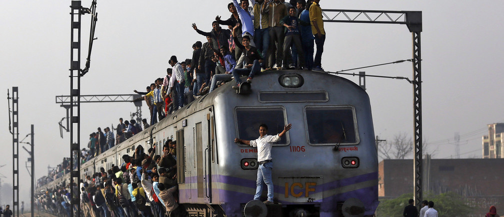Passengers travel on an overcrowded train on the outskirts of New Delhi February 26, 2015. India will increase investment in its overloaded railway network to 8.5 trillion rupees ($137 billion) over the next five years, the government said on Thursday, promising to modernise existing tracks and introduce faster trains. REUTERS/Ahmad Masood (INDIA - Tags: BUSINESS TRANSPORT POLITICS TPX IMAGES OF THE DAY) - GM1EB2Q19AH01
