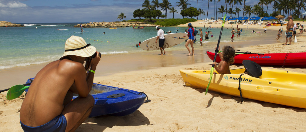 Mike Wilson takes a picture of his son playing in a kayak on the beach as two hurricanes approach the Hawaiian islands, in Honolulu, Hawaii, August 6, 2014. Hawaiians braced for a one-two punch from a pair of major storms headed their way on Wednesday, as Hurricane Iselle bore down on the islands packing high winds and heavy surf and Julio, tracking right behind, was upgraded to hurricane status.  REUTERS/Hugh Gentry (UNITED STATES - Tags: ENVIRONMENT DISASTER SOCIETY) - RTR41I39