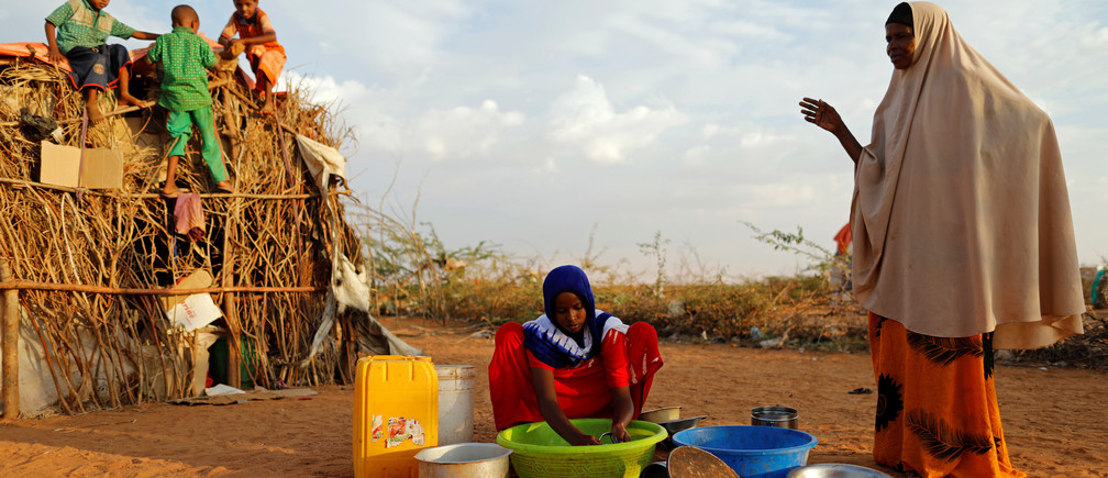 """Zeinab, 14, (C) washes dishes as her mother Abdir Hussein gestures and her nephews play at a camp for internally displaced people from drought hit areas in Dollow, Somalia  April 3, 2017. REUTERS/Zohra Bensemra    SEARCH """"ZEINAB DOLLOW"""" FOR THIS STORY. SEARCH """"WIDER IMAGE"""" FOR ALL STORIES. - RTX34W4Z"""