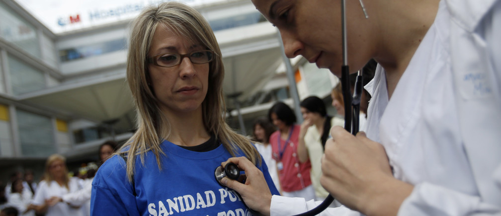 "A health worker pretends to be a doctor using a stethoscope on a patient during a protest against the local government's plans to cut public healthcare spending outside Infanta Leonor hospital in Madrid May 7, 2013. The T-shirt reads, ""Public health for all"". REUTERS/Sergio Perez  (SPAIN - Tags: HEALTH POLITICS BUSINESS CIVIL UNREST) - RTXZDH7"