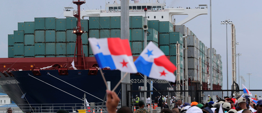 People wave Panama flags as they wait for the Chinese COSCO container vessel named Andronikos to navigate through the Agua Clara locks during the first ceremonial pass through the newly expanded Panama Canal in Agua Clara, on the outskirts of Colon City, Panama June 26, 2016.
