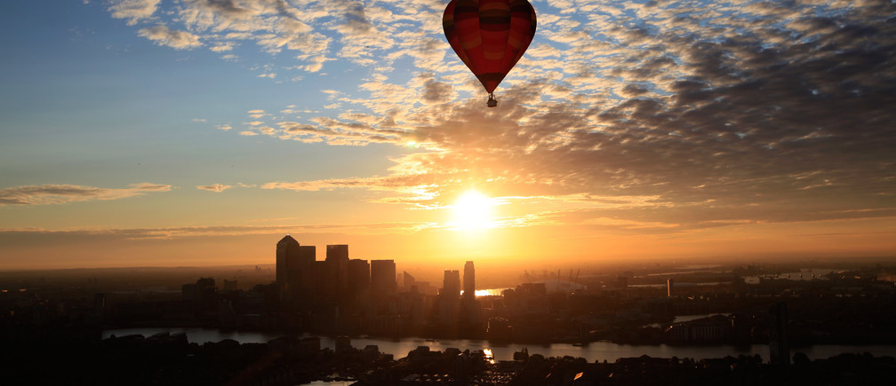 A hot air balloon rises into the early morning sky in front of the Canary Wharf financial district of London, July 25, 2011.