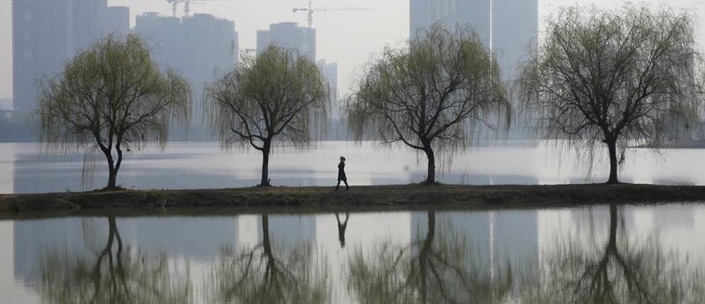A woman walks past trees reflected on a lake in front of a construction site of a residential compound on a hazy day in Wuhan, Hubei province March 6, 2015. China aims to grow its economy by around 7 percent in 2015 and to keep consumer inflation at around 3 percent, Premier Li Keqiang said in remarks prepared for delivery at today's opening of the annual meeting of parliament, the National People's Congress. REUTERS/Stringer (CHINA - Tags: ENVIRONMENT BUSINESS CONSTRUCTION REAL ESTATE TPX IMAGES OF THE DAY) CHINA OUT. NO COMMERCIAL OR EDITORIAL SALES IN CHINA - GM1EB36182X01